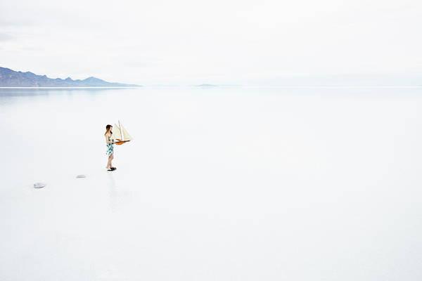 Wall Art - Photograph - Woman On Path In Lake Holding Model by Thomas Barwick