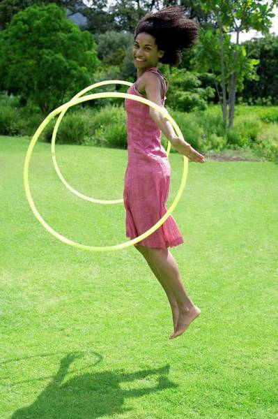 Hula Wall Art - Photograph - Woman Playing With Hula Hoops by Ian Hooton/science Photo Library