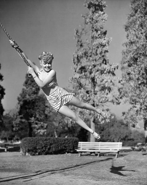 Exertion Wall Art - Photograph - Woman Swinging On A Rope by Underwood Archives