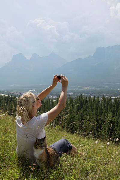 Wall Art - Photograph - Woman Takes Photo With Cat In Mountain by Philip & Karen Smith / TFA