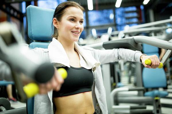 Self Confidence Photograph - Woman Using Shoulder Press Machine by Science Photo Library