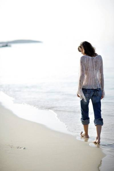 Paddling Photograph - Woman Walking Along A Beach by Ian Hooton/science Photo Library