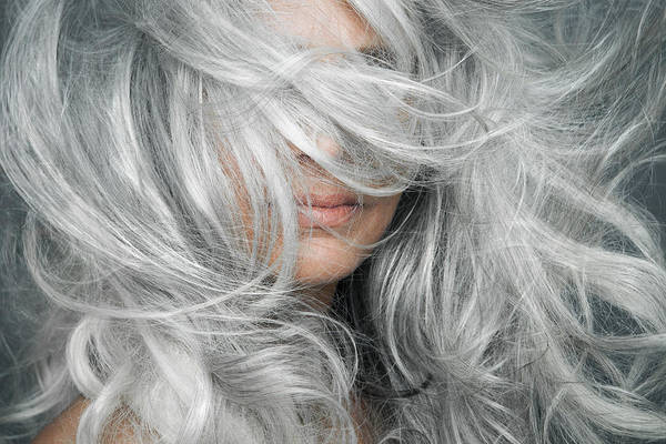 Woman With Grey Hair Blowing Across Her Face. Art Print by Andreas Kuehn