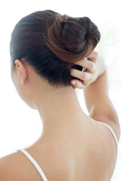 Buns Photograph - Woman With Hair Bun Scratching Head by Science Photo Library