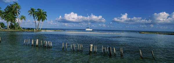 Sea Of Serenity Photograph - Wooden Posts In The Sea With A Boat by Panoramic Images