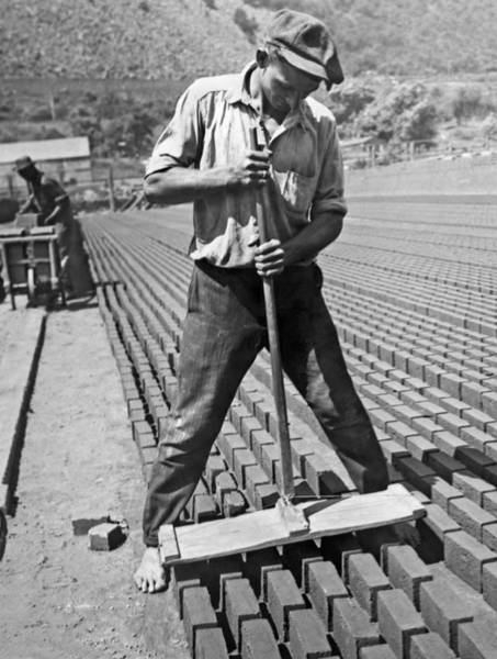 1924 Photograph - Worker Stamping Out Bricks by Underwood Archives