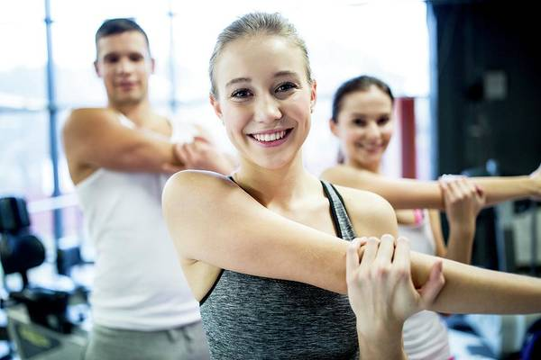 Self Confidence Photograph - Young Adults Doing Warm Up Exercise by Science Photo Library
