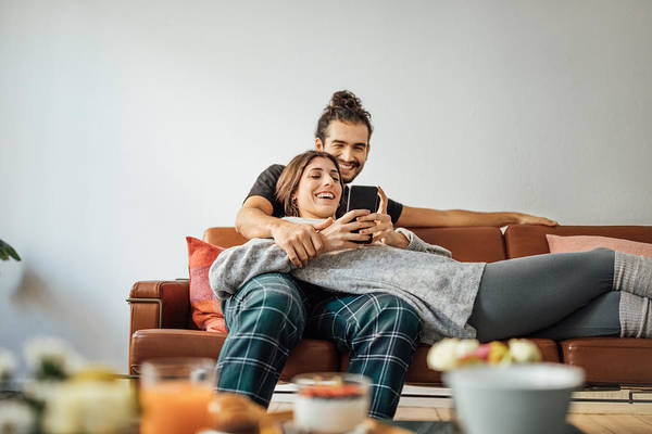 Young Couple With Smart Phone Relaxing On Sofa Art Print by Luis Alvarez