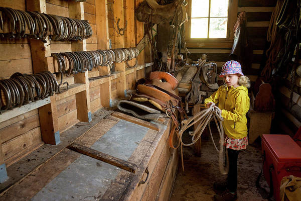 Wall Art - Photograph - Young Girl Coiling Rope In Tack Room by Kennan Harvey