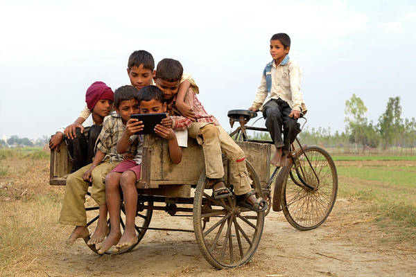 Casual Photograph - Young Indian Boys Looking At Tablet by Adrian Pope