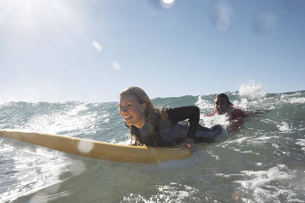 Young Man Being Towed In Sea By Young Woman On Surfboard, Smiling Art Print by Anthony Ong