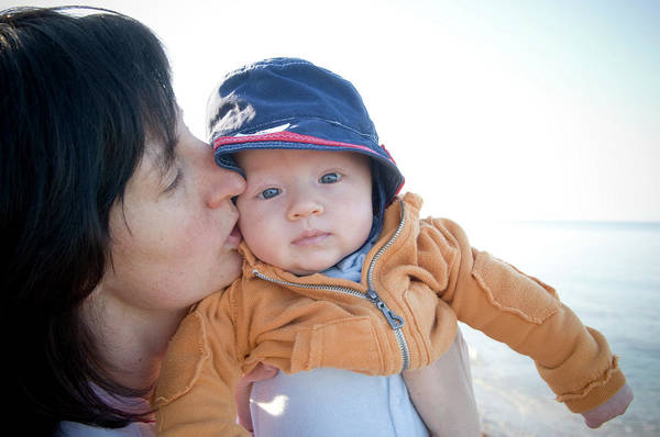 Wall Art - Photograph - Young Mother Kissing Babys Cheek While by David Nevala