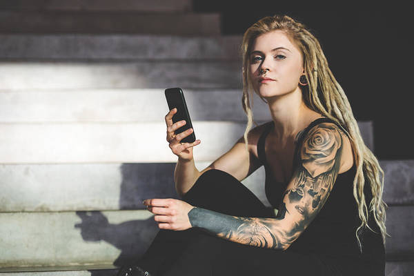 Young Tattooed Woman Texting Message On Mobile Phone Art Print by Nikada