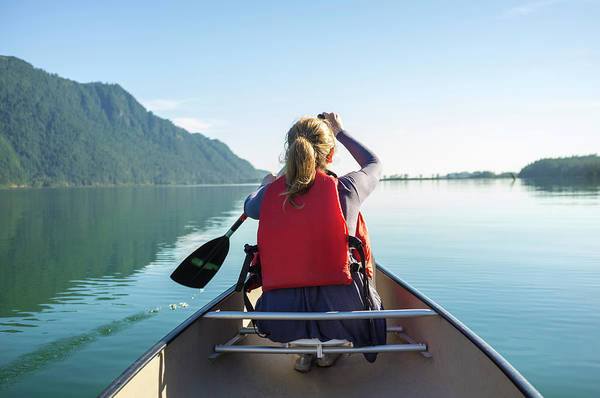 Canoe Photograph - Young Woman Paddling A Canoe On A Lake by Laara Cerman/leigh Righton