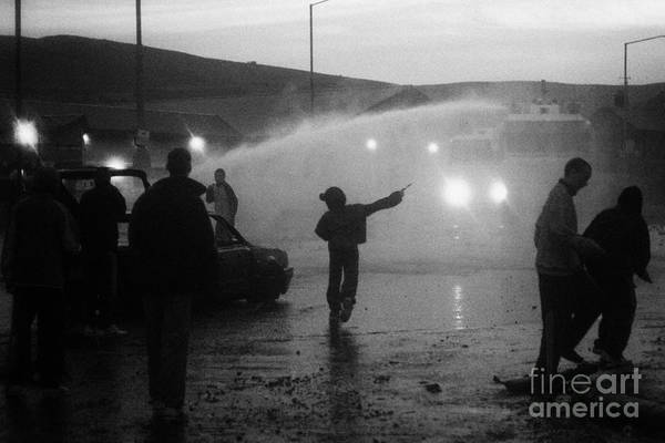 Turmoil Photograph - Youths Rioting Throwing Stones With Burned Out Car Being Hit By Water Canon On Crumlin Road At Ardoy by Joe Fox
