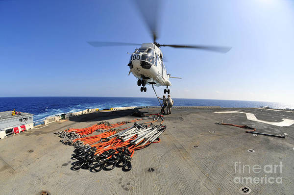 Amphibious Assault Ship Wall Art - Photograph - Airmen Attach Pallet Rigs To An Sa-330j by Stocktrek Images