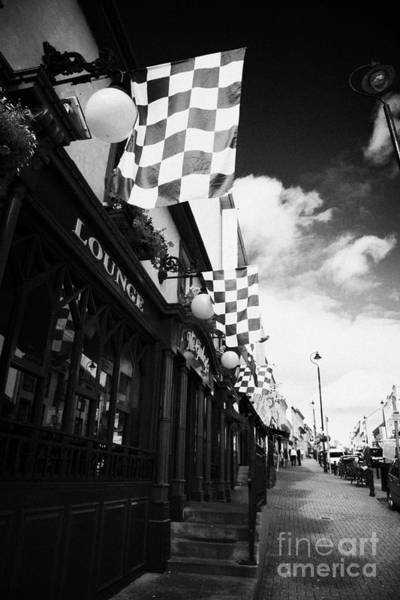 Flying The Flag Wall Art - Photograph - Green And Yellow Donegal Colours Flags Outside Bar On Main Street Letterkenny County Donegal by Joe Fox