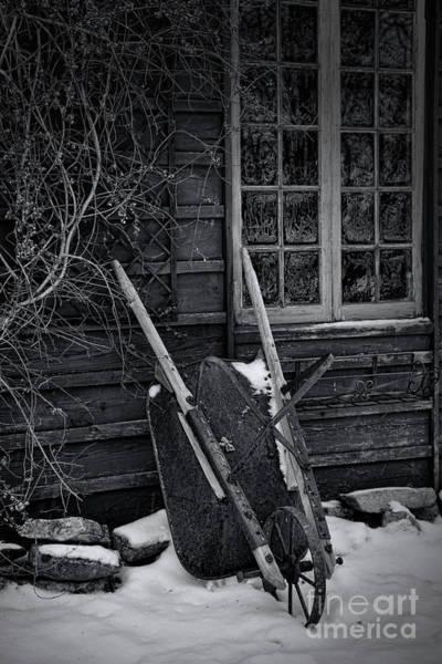 Photograph - Old Wheelbarrow Leaning Against Barn In Winter by Sandra Cunningham