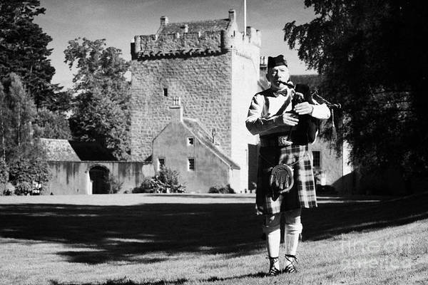 Bagpipe Wall Art - Photograph - scottish bagpipe player playing pipes in front of kilravock castle Scotland uk united kingdom by Joe Fox