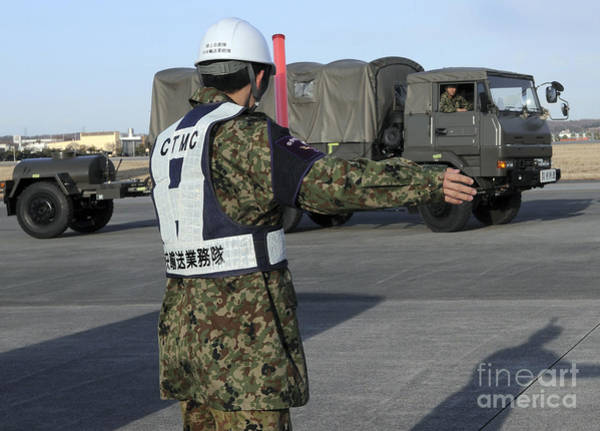 Utility Aircraft Photograph - A Japanese Soldier Marshals Vehicles by Stocktrek Images