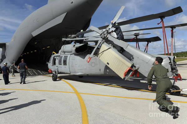 Military Air Base Photograph - A Helicopter Is Loaded Onto A C-17 by Stocktrek Images