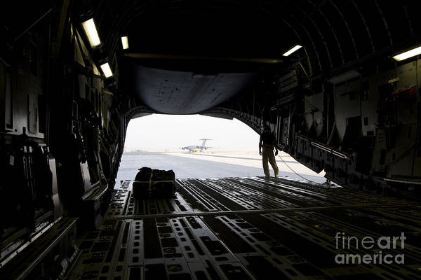 Photograph - A Loadmaster Guides The Pilot Of A C-17 by Terry Moore