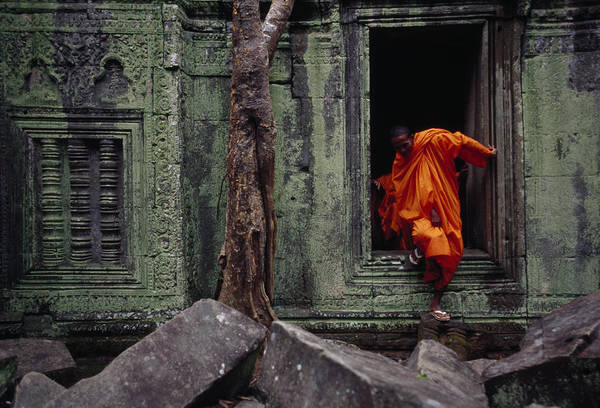 Wall Art - Photograph - A Monk Emerges From The Doorway Of An by Steve Raymer