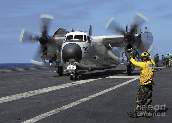 Uss George Washington Wall Art - Photograph - A Sailor Gives Hand Signals by Stocktrek Images
