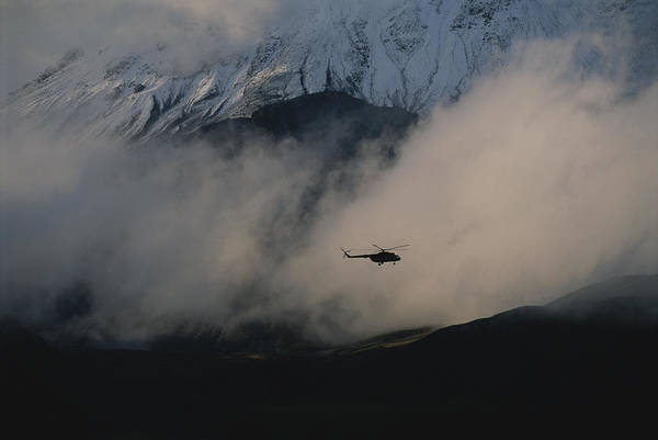Kamchatka Photograph - A Silhouetted Helicopter Flies by Carsten Peter