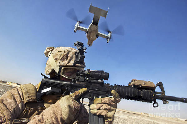Mv-22 Photograph - A Soldier Provides Security As An Mv-22 by Stocktrek Images