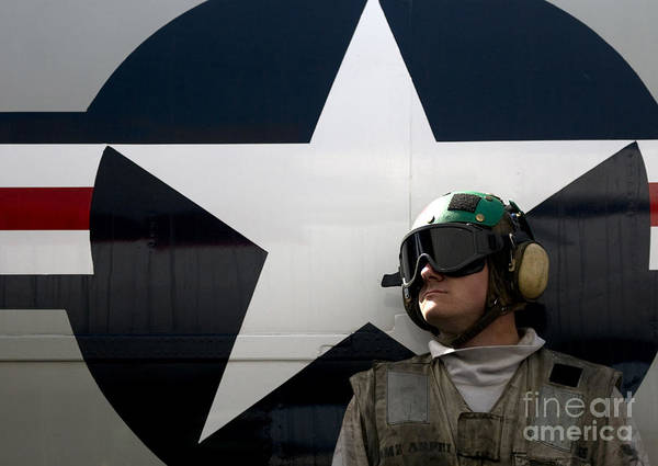 Uss Carl Vinson Photograph - An Airman Stands In Front Of A C-2a by Stocktrek Images