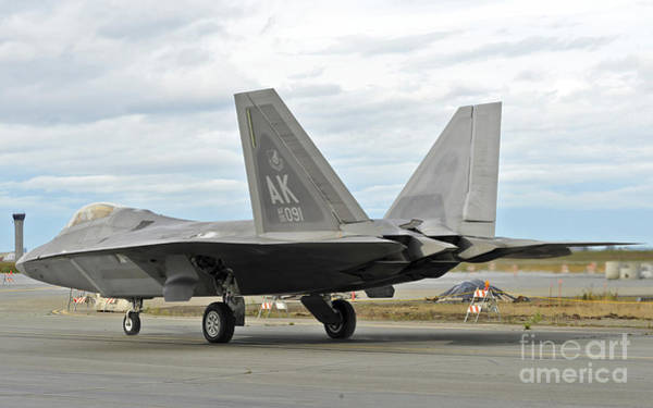 Elmendorf Photograph - An F-22 Raptor Taxis The Runway by Stocktrek Images