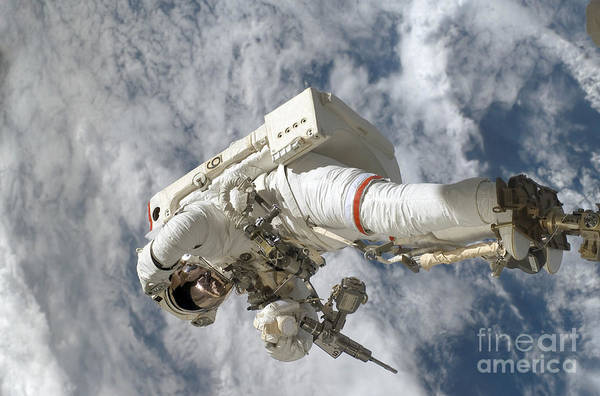 Photograph - Astronaut Anchored To A Canadarm2 by Stocktrek Images