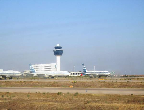 Photograph - Athens Airport Airplanes On The Taxiway Runway Getting Ready To Take Off by John Shiron