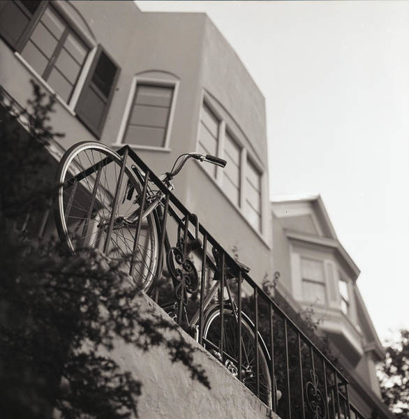 Fence Photograph - Bike Locked On Fence Against House by Copyright Ricky G. Brown 2011