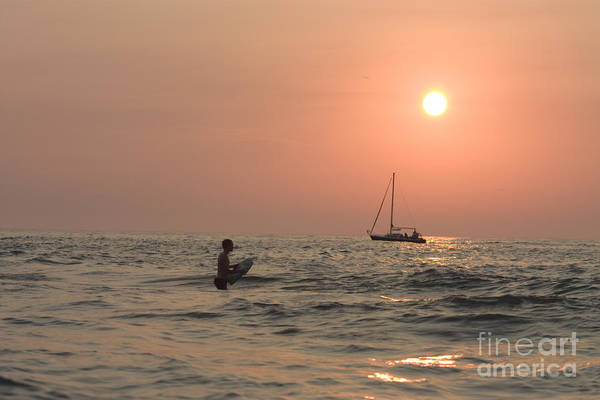 Bodyboard Photograph - Boy Swimming Near Sailboat At Sunset by Christopher Purcell