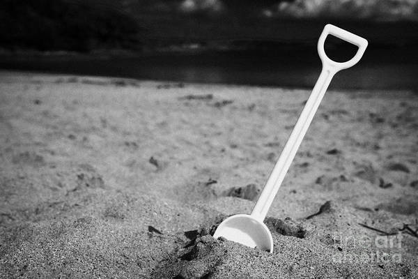 Wall Art - Photograph - Childs Toy Plastic Spade Stuck Into The Sand On A Beach by Joe Fox