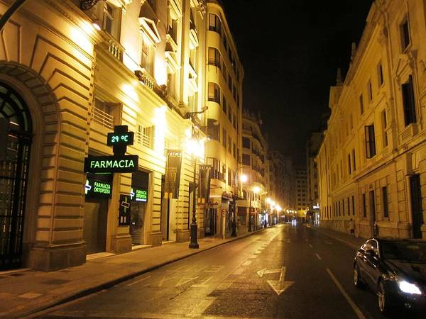 Photograph - Farmacia Pharmacy On Local Street Of Valencia With Lamp Posts At Night In Spain by John Shiron
