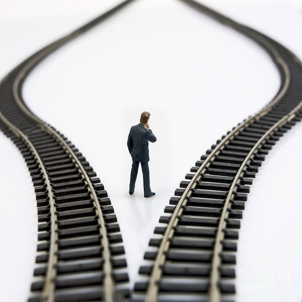 Out Of Business Wall Art - Photograph - Figurine Between Two Tracks Leading Into Different Directions  Symbolic Image For Making Decisions by Bernard Jaubert