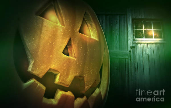 Photograph - Glowing Pumpkin At Night In Front Of Barn Door by Sandra Cunningham