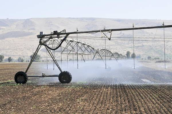 Kibbutz Photograph - Irrigation Robot Watering A Fiel by Photostock-israel