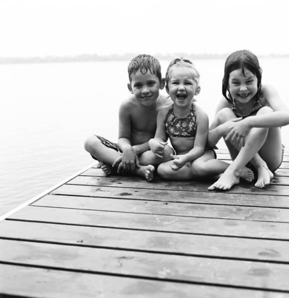 Door To Door Photograph - Kids Sitting On Dock by Michelle Quance