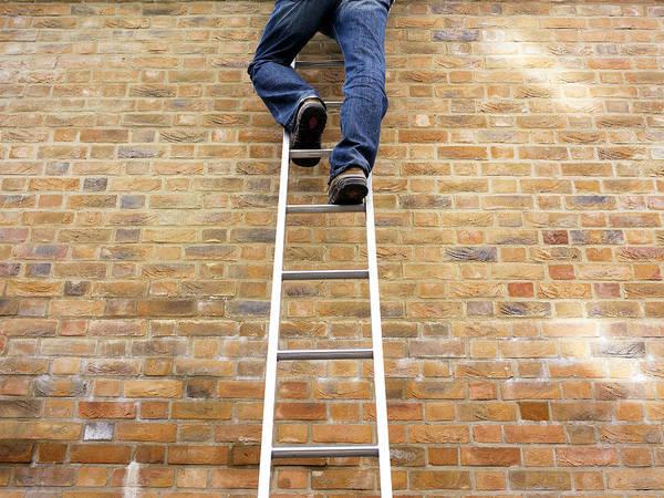 Rungs Wall Art - Photograph - Man Climbing A Ladder by Tony Mcconnell