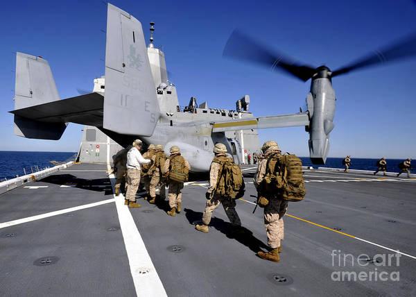 Mv-22 Photograph - Marines Board An Mv-22 Osprey Aboard by Stocktrek Images