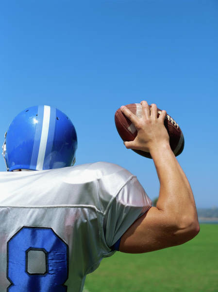 Football Helmet Photograph - Rear View Of A Football Player Throwing A Football by Stockbyte