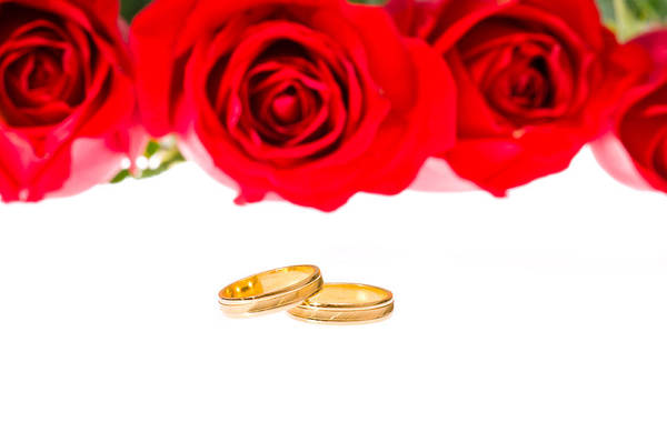 Photograph - Red Roses And Wedding Rings Over White by U Schade