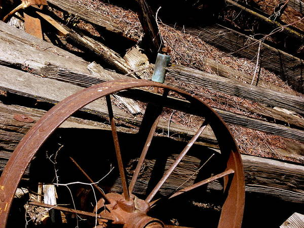 Photograph - Rusty Wooden Wagon Wheel by Jeff Lowe