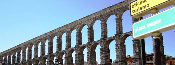 Photograph - Segovia Ancient Roman Aqueduct V A Water Conveyance Granite Stone Structure With Arches In Spain by John Shiron