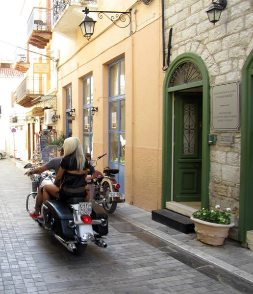 Photograph - Girl Riding On Motorcycle With Handsome Bike Rider Speed Stone Paved Street In Nafplion Greece by John Shiron