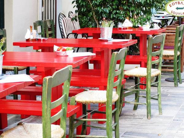 Photograph - Sidewalk Cafe Red Table Green Chair Set Up In Nafplion Greece by John Shiron